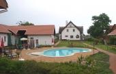 A medence a vendégházak, a főépület és a kerti grillező között